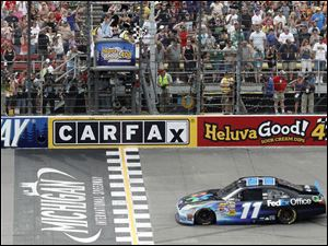 Denny Hamlin crosses the finish line to win the NASCAR Sprint Cup Series race at Michigan International Speedway.