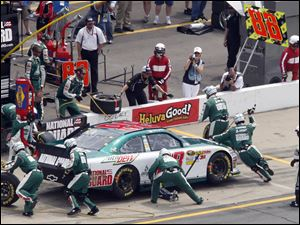 Dale Earnhardt, Jr. goes into the pit where his crew works on his car during the NASCAR Sprint Cup Series race at Michigan International Speedway.