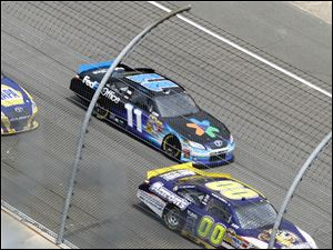 Denny Hamlin (11) who won the race, speeds around the track with Martin Truex Jr. (56) and David Reutimann (00).