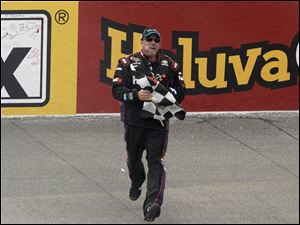 A crew member for Denny Hamlin runs the flag across the track for Hamlin to have in the winners circle.