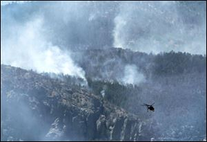 The battle against the Monument fire takes to the air Monday. Air crews had been grounded for most of Sunday. Firefighting efforts have been dogged for days by hot, windy weather.