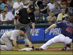Colorado Rockies third baseman Ty Wigginton, left, tags out Cleveland Indians' Travis Hafner (48) trying to go first to third on an RBI-single by Shin-Soo Choo in the sixth inning.
