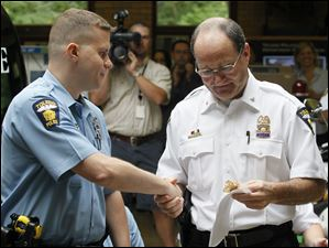 Toledo Police Officer David Wieczorek, left, is promoted to sergeant by Chief Mike Navarre