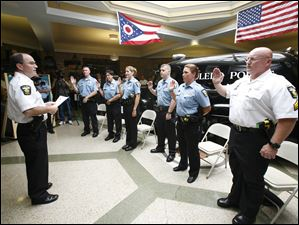 Chief Mike Navarre, left, administers the oath of a police officer to newly promoted sergeants from left, Eric Kenney, Sue Surgo, Jill Mannebach, David Wieczorek, and Danielle Kasprzak, and newly promoted Lt. John Anderson.