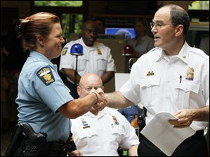 Toledo Police Chief Mike Navarre, right, shakes the hand of Officer Danielle Kasprzak as she is promoted to sergeant.