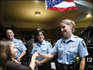 Madison Mannebach, 10, congratulates her mother, Sgt. Jill Mannebach, after she was promoted. Looking on are officers Eric Kenney, back left, and Sue Surgo, who also were also promoted to sergeant..