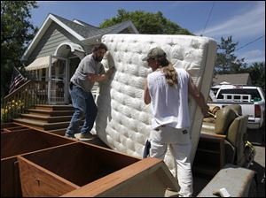 Mike Mertz, left, and Chris Delker load a mattress onto a trailer as they help Chris' father evacuate his Minot, N.D., home Thursday.