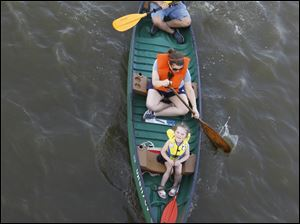Dave Zobler, top, Andrea Zimmerman, center, and her daughter Zoe Zimmerman, 3, paddle a canoe on the Ottawa River.