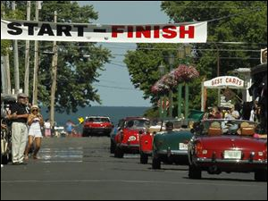 Tourists watch as the historic, foreign cars in the Put-in-Bay Road Race parade finish their first lap around the race route on the Ohio island.