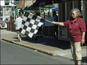 Mary Costich, from New Hampshire, holds the checkered flag as the car cross the finish line downtown.