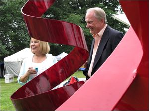 Sue and Larry Mullins are framed by a sculpture at the Crosby Festival preview party at Toledo Botanical Garden.