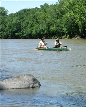 Matt Horvat dusts off his hat while on a bankside break during Tuesday's nearly 32-mile paddle down the Maumee River.