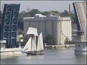 The ship fires a cannon as it sails through the raised Cherry Street bridge.