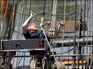 One of the sailors on Lynx works on the rigging as the ship pulls into Toledo on the Maumee River.