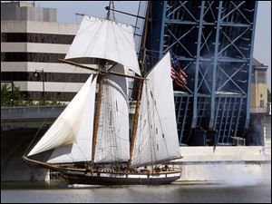 The Privateer Lynx sails under the MLK Bridge with smoke floating out of the back form a salute from her main battery of 6-pounder carronades upon her grand entrance into Toledo.