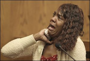 Gladys Wade demonstrates how she says she was choked by Anthony Sowell as she testifies during his trial Thursday in Cleveland.