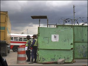 The entrance to the dump is protected by a wall, barbed wire, and armed guards.