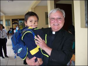 The Rev. Donald Vettese, founder of International Samaritan, holds 3-year-old Anibal Pacheco at the Santa Clara nursery in Guatemala City. The former president of St. John's Jesuit High School has been working for 16 years to help the poorest of the poor escape poverty through education.