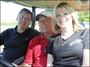 Glenn Badenhop, left, Tim Toland, center, and Jerri Ryan ride in a golf cart during the Savage Foundation Golf Classic at the Belmont Country Club.