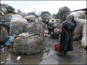 Middlemen on the outskirts of the dump get their goods ready for delivery to recycling companies.