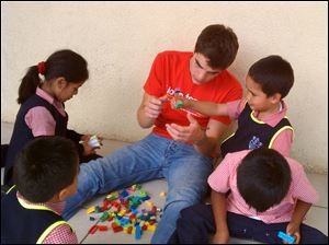 Ross Satler plays Legos with Santa Clara nursery students.
