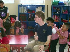 Guatemalan schoolchildren hang on to St. John's student Sean Burlingame, who said they made him feel like Justin Bieber.
