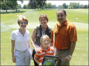 Alliene Liden, left, Sheila Schwartz, center, and Ramy Eidi, right, pose with Tucker Welty, 7, front, during the Toledo Children's Hospital Golf Benefit.
