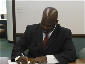 Mayor Mike Bell signs the paperwork for the sale of the Marina District to Dashing Pacific Group, Ltd., in Toledo Saturday, shortly before the Chinese company unveils their plans for the site.