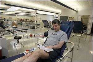 Robert Harden of Toledo, a dedicated donor, reads while donating blood at the American Red Cross blood center on Executive Parkway. The Western Lake Erie Blood Services Region for northwest Ohio and southeast Michigan is keeping its donation centers open  throughout the holiday weekend.