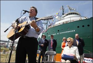 Russ Franzen sings during the rechristening of the SS Willis B. Boyer to SS Col. James M. Schoonmaker, at International Park in Toledo on Friday.  Watching from back left are, James M. Schoonmaker II,  Paul LaMarre, III, executive director of the Col. James M. Schoonmaker Museum Ship, Treecie Schoonmaker, wife, of James, U.S. Rep. Marcy Kaptur, seated, and Chris Gillcrist, executive director of the Great Lakes Historical Society.