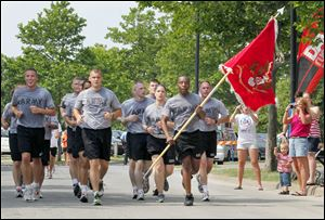 SSG Dale Nelson, front,  holds the 983rd Engineer Battalion flag, which is in Monclova, Ohio, as members of his battalion run to the finish line together during the first annual Heroes Run through the streets of downtown Toledo on July 2, 2011.