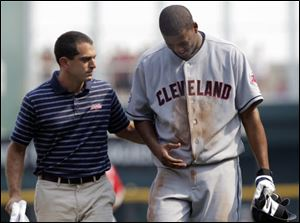 Trainer Lonnie Soloff, left, helps Cleveland Indians starting pitcher Fausto Carmona walk off the field with an undisclosed injury during a game against the Cincinnati Reds on Saturday.