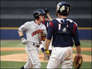 Toledo catcher Max St. Pierre watches as Indians player Brian Friday crosses home plate after hitting a solo home run in the sixth inning.