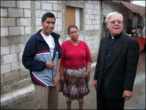 Marvin Yup, 18, his mother, Rosa Yup, meet the Rev. Vettese in the street in their neighborhood near the city dump.