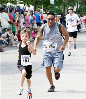 Owen Dennis, 6, of Perrysburg, gives it his all as he crosses the finish line ahead of Javier Martinez of the Marine Corps.