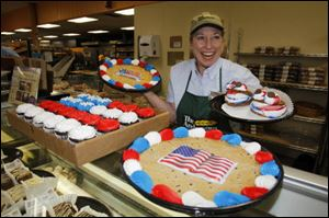 Bakery manager Linda Jones displays holiday-themed cookies and cupcakes for sale at The Andersons in West Toledo.