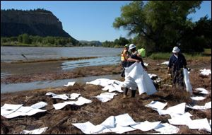ExxonMobil contractors clean up oil along the banks of the Yellowstone River in Billings, Mont., Sunday.