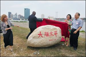Mayor Mike Bell and Dashing Pacific's Wu King Hung unveil a symbolic rock as Toledo Zoo Director Ann Baker, left, and Dashing Pacific's Yuan Xiaohong watch.