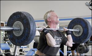 Weightlifter Jerry Huth, 56, is midway through the clean-and-jerk maneuver and will complete the lift by thrusting the 210 pounds of weight directly over his head with his arms fully extended.