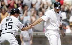 Detroit Tigers' Brandon Inge, left, and Jhonny Peralta celebrate after scoring on a single by Magglio Ordonez to take a 4-3 lead in the seventh inningagainst the San Francisco Giants. The Tigers won, 6-3.