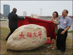 Toledo Mayor Mike Bell, Tina Yuan (Yaun Xiaohong) and Wu King Hung unveil a symbolic rock at the Marina District.