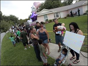 A group of neighbors and visitors stand across the street from the George and Cindy Anthony residence as most express their disagreement with the Casey Anthony verdict in Orlando, Fla. Casey Anthony was found not guilty of first-degree murder, aggravated manslaughter and aggravated child abuse.