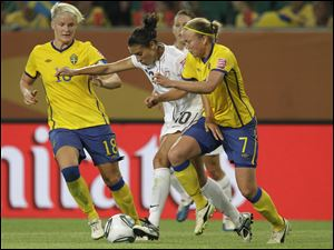 United States' Carli Lloyd, center, fights for the ball between Sweden's Nilla Fischer  and Sweden's Sara Larsson, right, during the group C match Wednesday.
