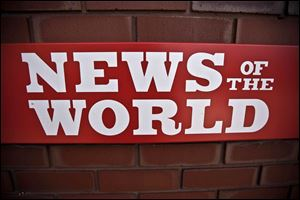 A News of the World sign hangs at the entrance to a News International building in London.