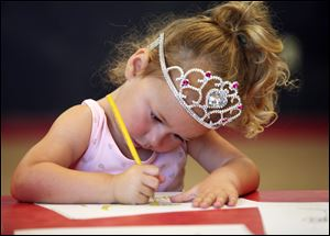 Reese Brennan, 3, prefers to wear her crown during a Safe-T-City class in Crossroads Community Church in Ottawa Lake, Mich. At the new school also, the Montessori method will let children learn in a relatively unstructured environment.