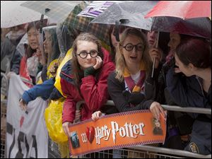 "Harry Potter fans wait with umbrellas in the rain outside the cinema in Leicester Square, central London, for the world premiere of ""Harry Potter and The Deathly Hallows: Part 2."""