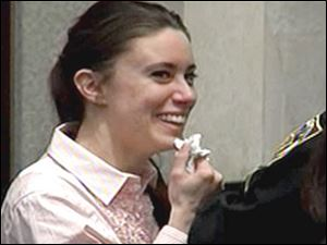 Casey Anthony smiles as she returns to the defense table Tuesday, in this image made from video, after being acquitted of murder charges at the Orange County Courthouse in Orlando, Fla.