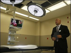 Sean Tucker, from medical device firm Steris Corp., demonstrates lighting equipment at Wildwood Orthopaedic and Spine Hospital.