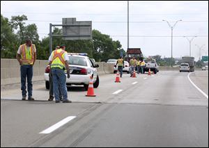 Ohio Department of Transportation workers examine the I-75 bridge joint at Lagrange Street.