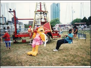 Birdie the Early Bird, a Ronald McDonald character, joins children on a swing ride at a Toledo festival.